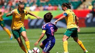 Aya Miyama #8 of Japan falls down as she is challenged by Caitlin Foord #9 and Lisa De Vanna #11 of Australia