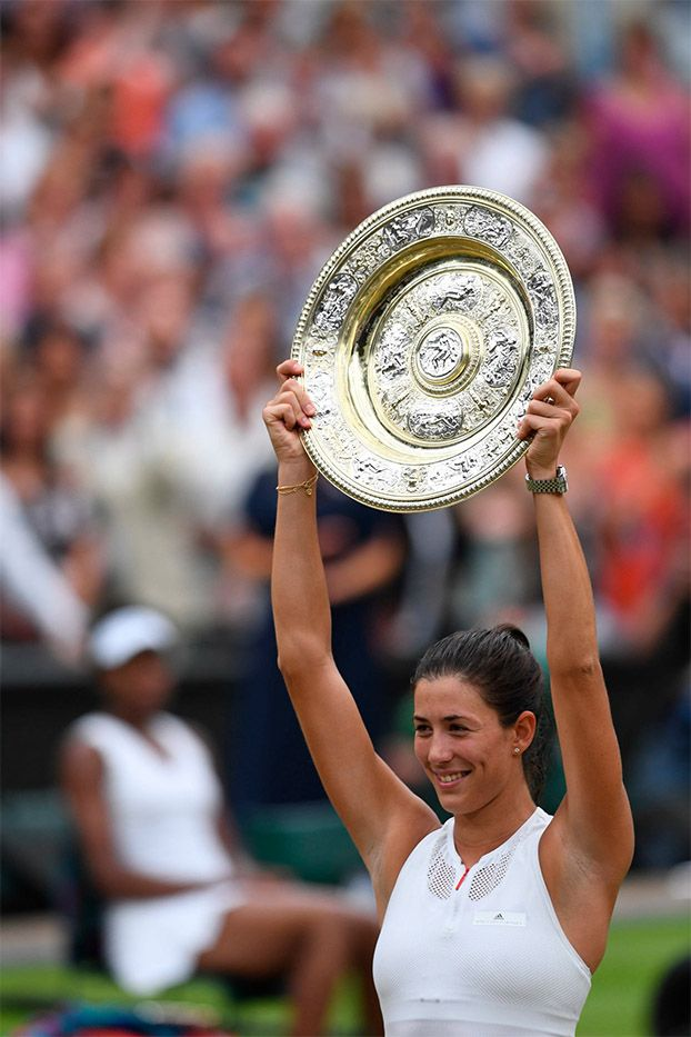 Garbiñe Muguruza lifts the Venus Rosewater Dish as she is crowned the Ladies' Singles Champion for 2017