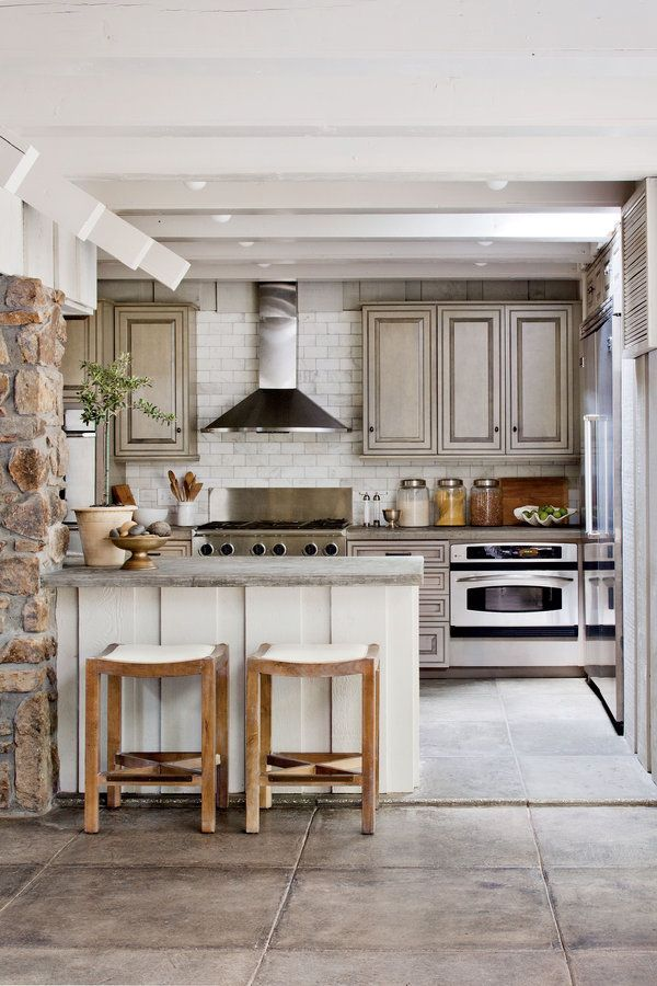 Hand-poured concrete countertops pick up the floor's gray tones in this kitchen designed by owner and Southern Living style director Heather Chadduck Hillegas.  See more of this Nature-Inspired Lake House