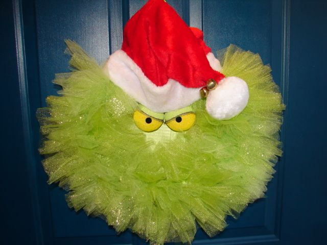 "Grinch Wreath using 14"" extruded Styrofoam base spray painted lime green. Tie 15"" strips of tulle around the base. Hot glue a circle of green painted cardboard to the back of the tulle covered base. Paint Styrofoam eyes half green and half yellow; add doll eyelashes and little black eyes and hot glue to upper part of green cardboard circle. Hot glue a Santa hat to the top. Attach a ribbon tie on the back and bells to the pom pom on the hat."
