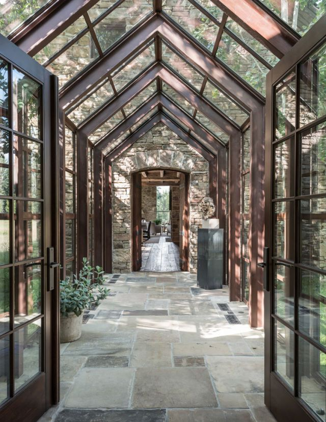 A modern glass and steel walkway connects the dairy barn to the rest of the 7,919-square-foot main house: a salvaged stacked log cabin containing the entryway and mudroom.