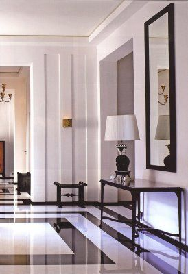 A modern, minimalist entryway done in black & white. The floor is splendid, with just a table, mirror & black lamp. simple yet very chic...V