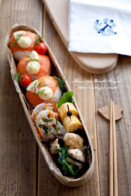 Salmon temari sushi bento box, featuring sides of tamagoyaki, carrot & lotus root miso salad, stir fried seafood & greens, and cherry tomatoes.