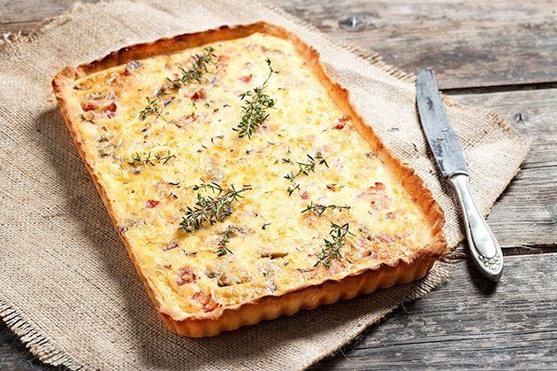 Για τη βάση Ξεπαγώνουμε την ζύμη για πίτσα. Πασπαλίζουμε λίγο αλεύρι στον πάγκο εργασίας. Ακουμπάμε την πίτσα. Πασπαλίζουμε με το τυρί. Πιέζουμε με τον πλαστή να ανοίξει η διάμετρος του φύλλου. Την βάζουμε σε ταρτιέρα μακρόστενη. Φροντίζουμε να ντύσουμε και τα πλαϊνά. Ακουμπάμε μεμβράνη ή λαδόκολλα πάνω στην ζύμη. Γεμίζουμε με βαρίδια μέχρι πάνω. Ψήνουμε …