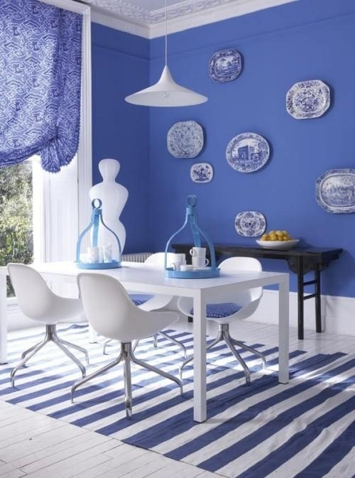 THIS color Blue!!! Cornflower blue walls, blue and white plates on walls, blue drapery, blue glass vessels, striped dhurrie rug, white furniture, dark wood sideboard