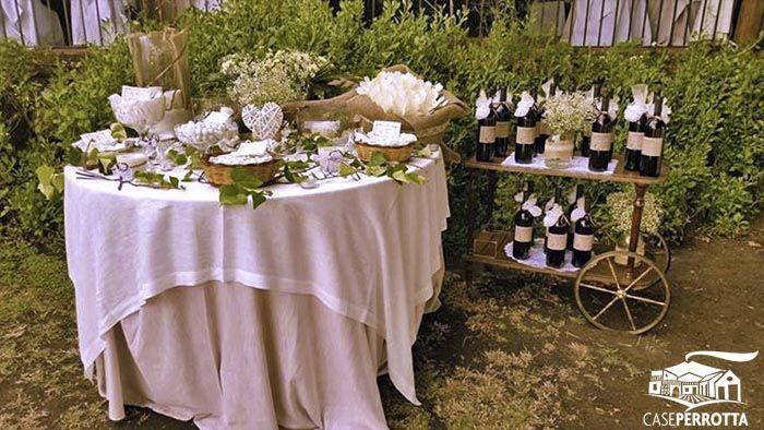 Confettata matrimonio sul prato con bottiglie di vino rosso come bomboniere