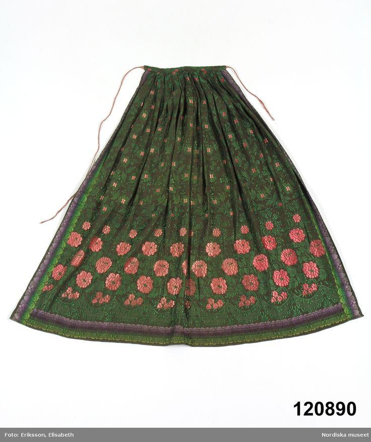 Förkläde, sannolikt ett brudförkläde  i halvsiden med avpassat mönster, varp av svart bomullsgarn. Öland.