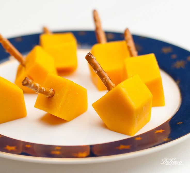 "Dreidel, dreidel dreidel, I made you out of CHEESE. We firmly believe that food should be fun. Here's a festive and easy snack the whole family can enjoy at holiday gatherings. Directions Order 1"" thick DI LUSSO® deli cheese slices. Mix and match cheeses. We love mild cheddar and Pepper Jack. Cut into cubes and trim cube ends at an angle. Insert pretzel sticks and serve."