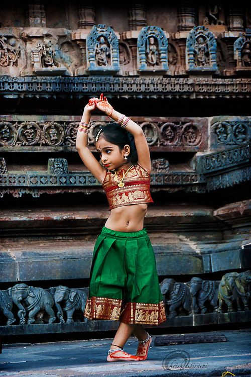 The little girl captured in this photograph is performing Bharat Natyam, a classic Indian dance form.