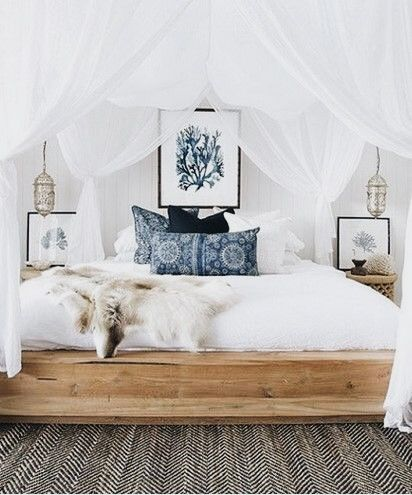 Canopy bed with white drapes and light washed wood bed frame