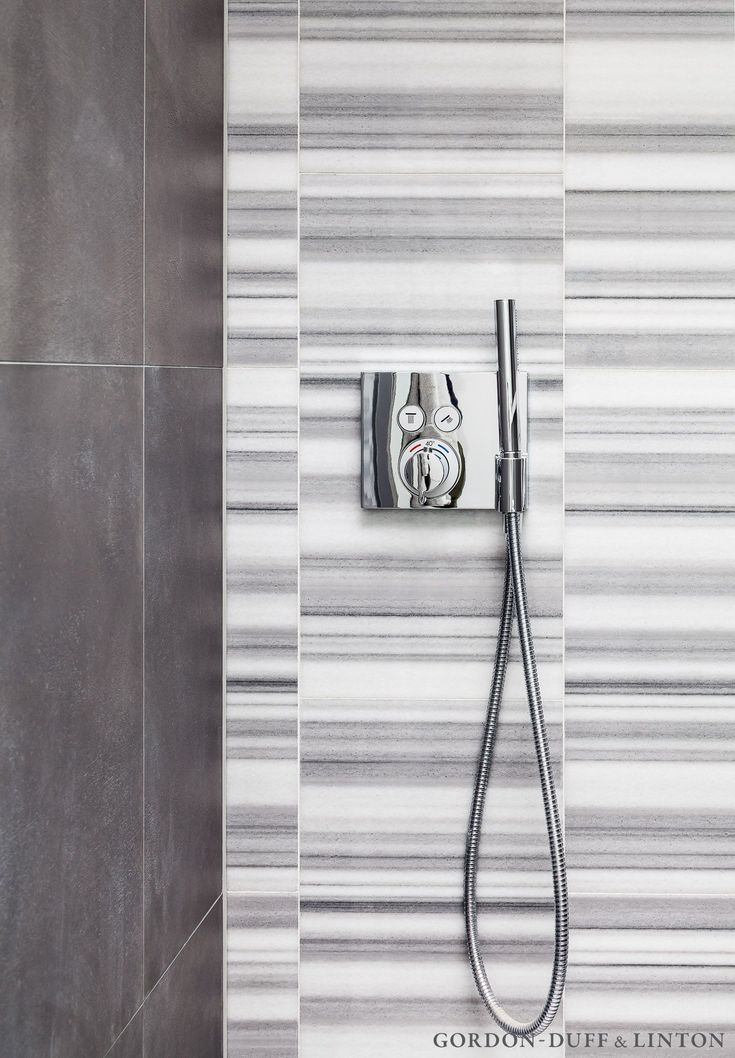Detail of the ensuite shower room featuring Striata marble tiles on the back wall and large format grey porcelain tiles on the other walls and floor. Hansgrohe brassware.