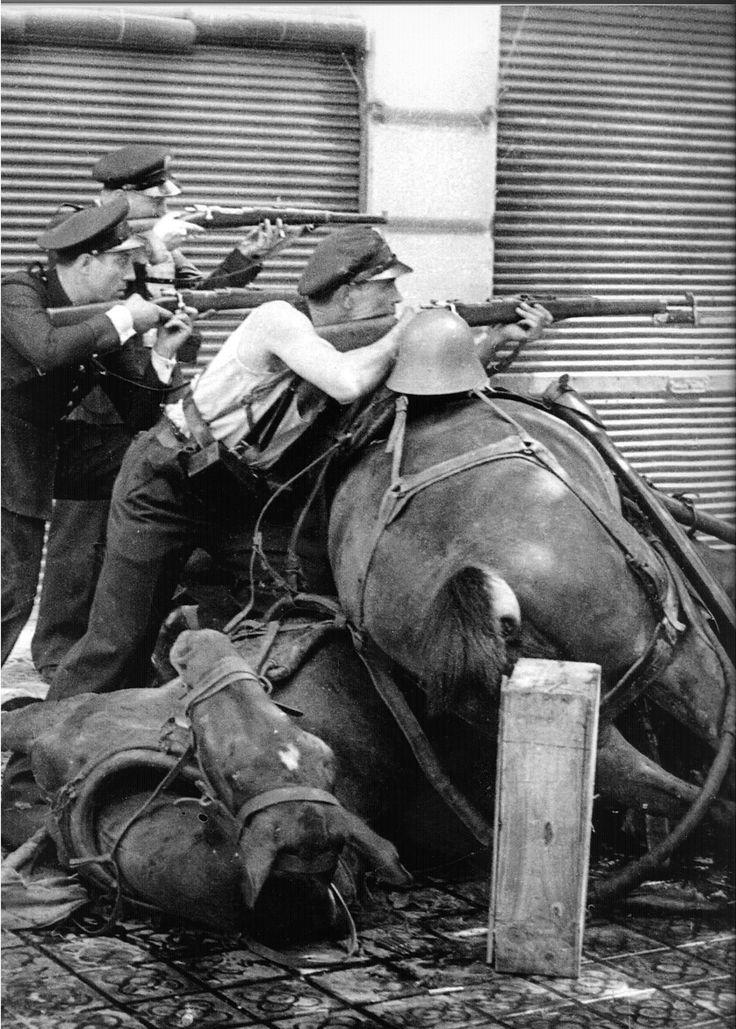 Agustí Centelles posiblemente el mejor fotógrafo español de la Guerra Civil Española.Esta imagen es una parte de una de sus más famosas fotografías. Les pidió a los guardias de asalto que posaran detrás de la barricada hecha con caballos muertos. En un principio los militares fieles a La República repelieron a los rebeldes en una lucha feroz. La fotografía está hecha en la calle Diputación de Barcelona en la mañana del 19 de Julio de 1936.