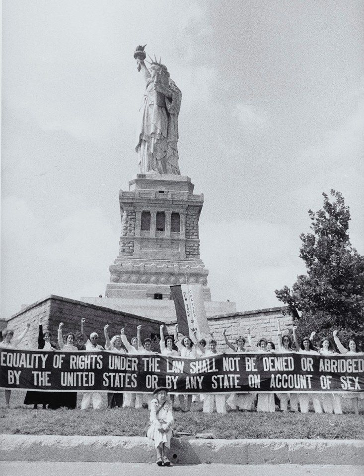 "Women with raised fists standing in front of the Statue of Liberty after a ""Women's Rights"" day march to the famous statue on August 26, 1978. They hold a banner reading ""Eq…"
