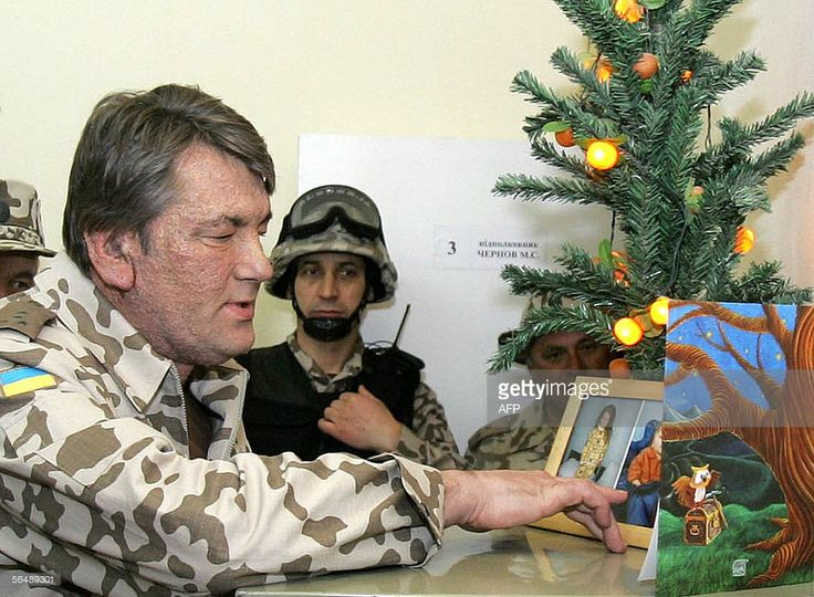 President of Ukraine Viktor Yushchenko (L) looks at pictures of soldier's children at a military base near the Shiite city of Kut, where Ukrainian troops have been stationed, 26 December 2005. Ukraine President Viktor Yushchenko arrived in Iraq on Monday for a surprise visit, as Ukraine wrapped up a withdrawal of most of its troops from the country. Yushchenko ordered Ukraine's troops out of the country earlier this year after assuming power in the ex-Soviet country following last year's…