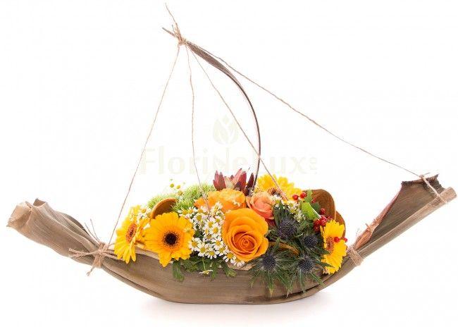 Barca cu flori de toamna, frunza de banan,  barca sustine intra panzele ei de sfoara flori de trandafiri, musetel, leucadendron, gerbera si eryngium, pentru a crea un aranjament floral de toamna perfect
