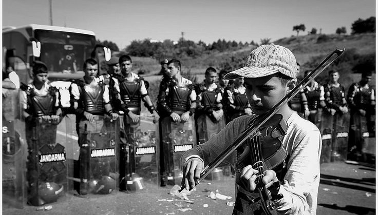 A young refugee plays violin in front of a line of Turkish police at Edirne,