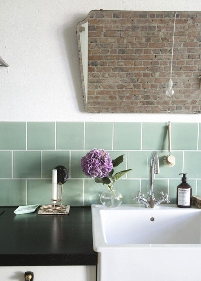 A white porcelain farm sink with a mint-green tiled backsplash gives the kitchen a fresh vintage look.