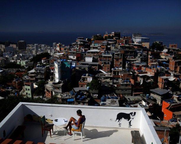 Les auberges de jeunesse à Rio de Janeiro  Une femme est assise sur la terasse de lauberge de jeunesse Tiki Favela de Cantagalo à Rio de Janeiro Brésil Avril 2016. Les auberges de jeunesse à Rio de Janeiro servent aussi de logements pas chers pour les plus aventureux parmi les 500.000 touristes étrangers attendus pour les Jeux Olympiques en Août. Les établissements souvrent également à la riche culture des bidonvilles de la ville pour les voyageurs leur donnant un aperçu des zones interdites…