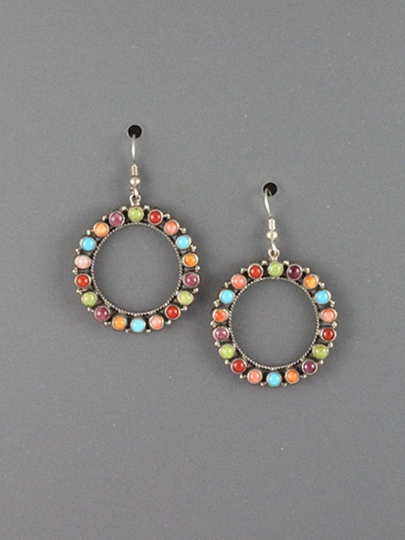 Round open center style cluster earrings with 18 settings in Orange and Purple Spiney Oyster Shell, Red and Pink Coral, Gaspeite, and Turquoise. These earrings measure 1 3/8 in diameter and are hung on sterling french earwires.