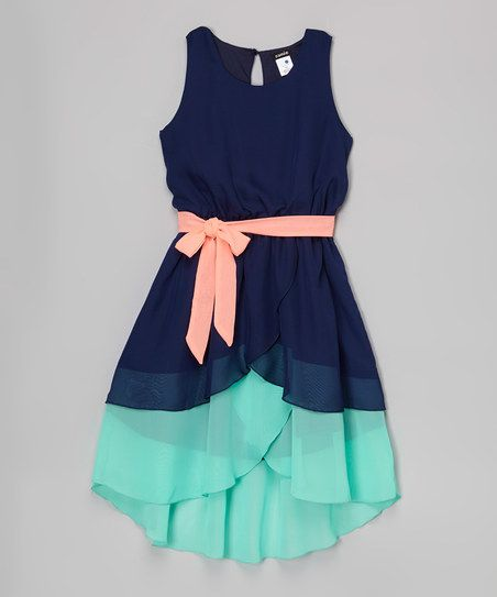Color block tiers bring breezy flair to this dress's hi-low silhouette, while a contrast belt cinches a perfect fit.