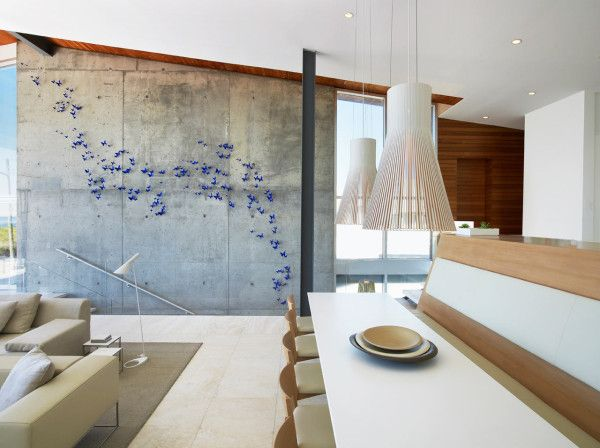 In this beach house on Long Island, designed by West Chin Architects & Interior Designers, the dining table is outfitted with half chairs and the other side has a bench for seating. Hanging about the white table are two Secto Lights.