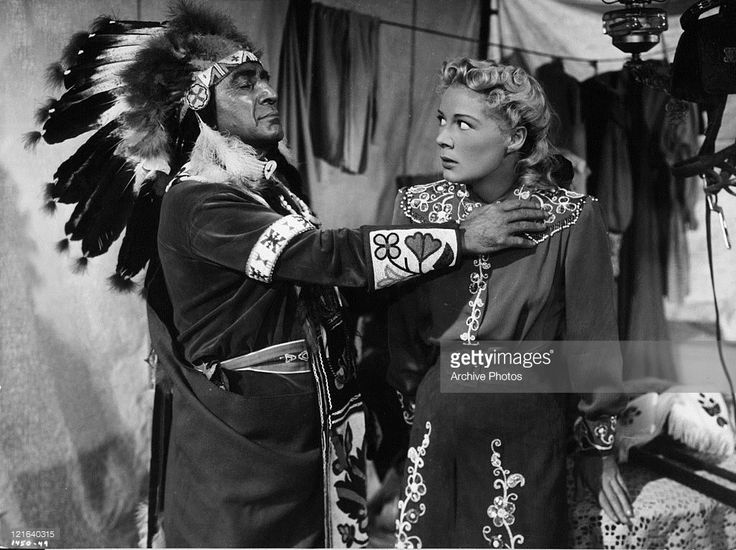 J Carrol Naish adopts Betty Hutton as a princess of his Sioux tribe in a scene from the film 'Annie Get Your Gun', 1950.