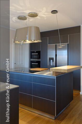 Die barplatte aus massivem birkenholz fügt sich elegant in das ensemble aus hochschränken und küchenblock ein