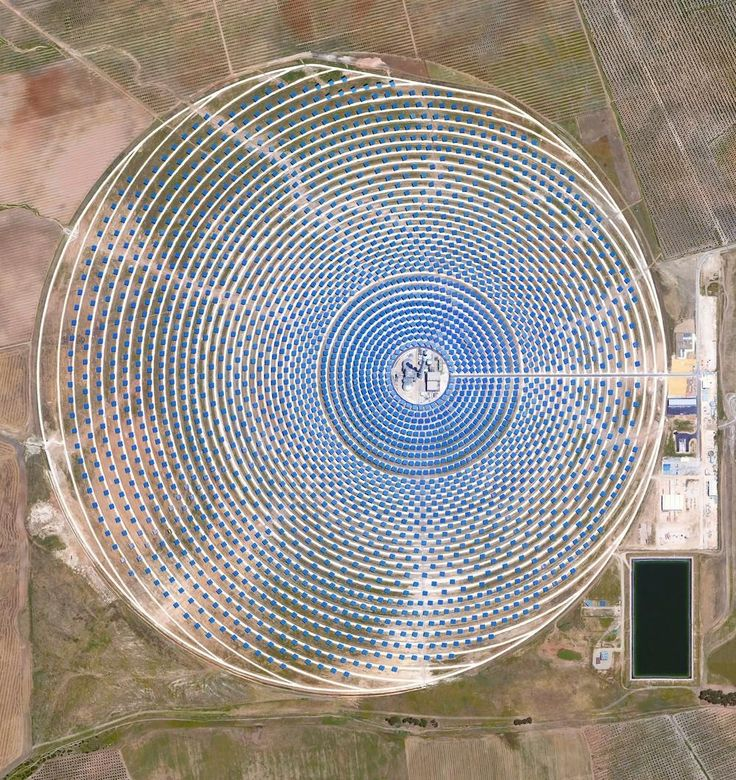 Gemasolar Thermosolar plant in Seville, Spain. The solar concentrator contains 2,650 heliostat mirrors that focus the sun's thermal energy to heat molten salt flowing through a 460-foot central tower. The molten salt then circulates from the tower to a storage tank, where it is used to produce steam and generate electricity. See more: http://www.vice.com/read/daily-overview-benjamin-grant-photos-space?utm_source=vicefbusads&utm_campaign=interest