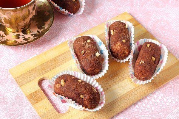 Пирожное «Картошка» из печенья  Ингредиенты: Печенье песочное - 600 грамм; Сгущенка - 1 банка; Масло сливочное - 200 грамм; Какао-порошок -3 ст.л; Ванилин - 1 пакетик.  Описание процесса приготовления: Этот вариант пирожного Картошка готовится из самых простых составляющий и основной - печенье. Печенье подойдет любое, например Юбилейное. Технология приготовления такого пирожного очень проста: оно крошится, затем скрепляется кремом из сгущёнки и сливочного масла. Попробуйте и Вы этот простой…
