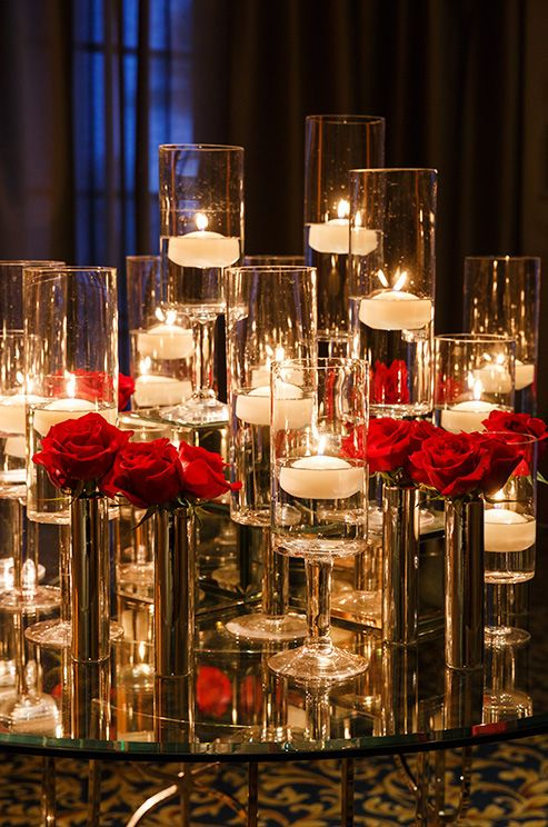 White floating candles are placed in tall glass stands and matched by metallic vases holding vibrant red roses.