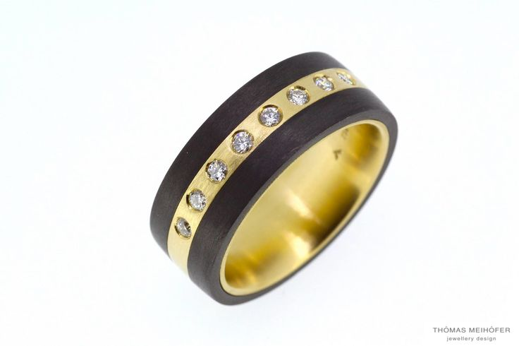 One of a kind custom made, carbon fibre, 18ct yellow gold and diamond band. We specialize in designing and making pieces a little bit outside the box!