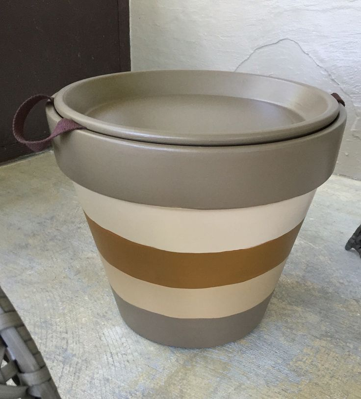 Large terra cotta pot I made into a table. I painted with left over pain samples. Then I added belt material for handles so the top comes off and the table doubles as storage.