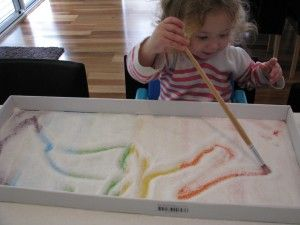Rainbow Salt Tray: glue strips of colored paper to the bottom of a tray, cover with a thin layer of salt and use finger or paint brushes to draw.