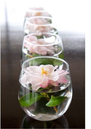 Simple centerpieces, flower floating in small vase ~looks like stemless wine glasses to me. Perfect!