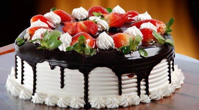 La torta di compleanno si prepara farcendo una torta al pan di spagna con una crema di mascarpone al cioccolato e decorando con bignè ripieni di crem...
