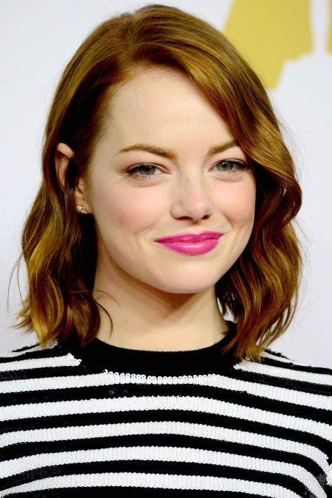 Emma Stone rocks a bright pink lip at the Oscar Nominee Luncheon.