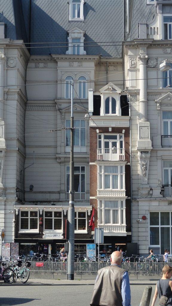 Lijn 9, halte 1 - Stationseiland. De door de bouwers van het Victoria Hotel ingekapselde pandjes, bekend uit de roman Publieke Werken van Thomas Roosenboom.