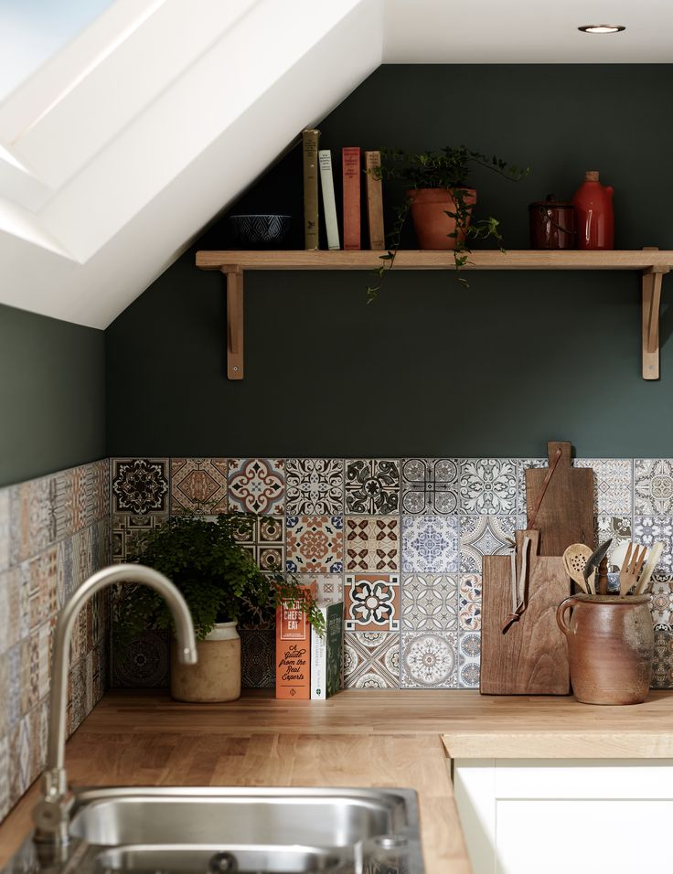 Mosaic tiles and an eclectic mix of crockery in earthy tones create a Mediterranean look in your shaker style kitchen. Off-cuts of wooden worktop can be used to create shelving. Take a look at more kitchen design ideas in the Shaker Collection by Howdens.