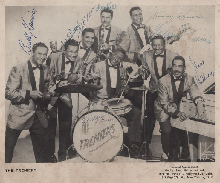 TRENIERS THE: Vintage signed 10 x 8 photograph by all eight members of the American Rhythm & Blues band The Treniers individually, comprising identical twins Cliff Trenier & Claude Trenier, their brothers Buddy Trenier & Milt Trenier, and other band members Jimmy Johnson (bass), Gene Gilbeaux (piano), Don Hill (sax) and Henry Green (drums). The promotional image depicts the band in a group pose together, in full length poses and each wearing identical suits, accompanied by their instruments.