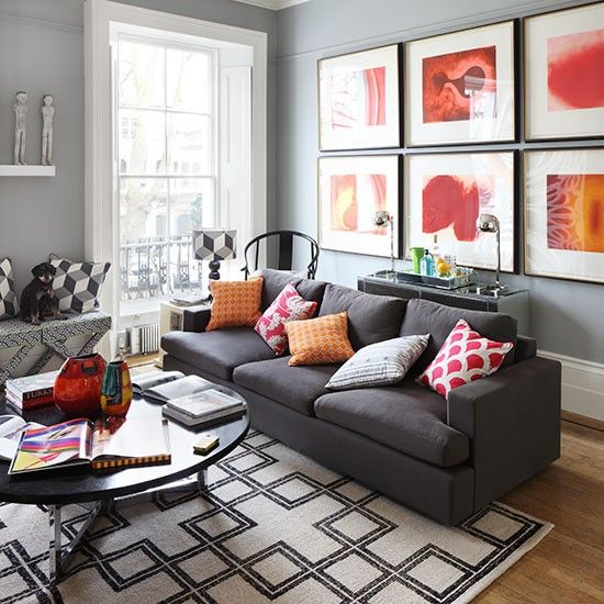 A Dramatic Wall Of Red And Orange Prints In The Living Room Brings Colour  To This