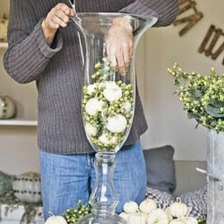 Mini white pumpkins with green berry in tall hurricane vase