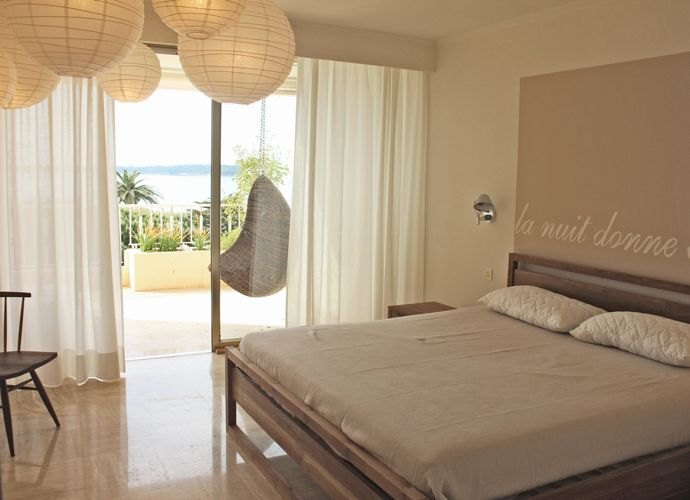 A fresh and seaside like house in Cannes by Nomade Architettura http://www.nomadearchitettura.com/#all  bedroom, hanging paper lamps, hanging chair, timber bed, text painted over the be