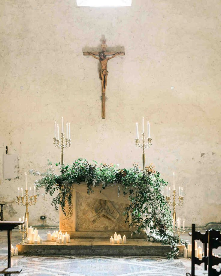 This Romantic Italian Wedding Features a Historic Venue—and One Amazing View | Martha Stewart Weddings - Trailing greenery and plenty of pillar candles adorned the altar of the intimate church.