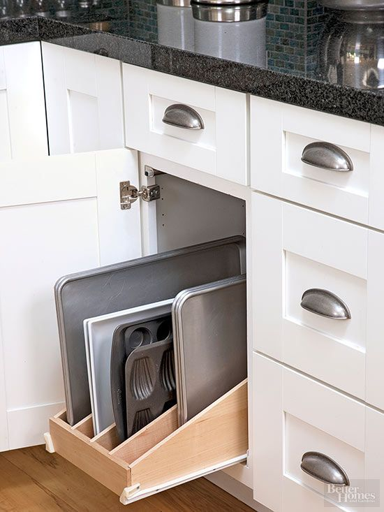 A divided pullout in a lower cabinet separates baking pans by size and type, standing them up to allow for quick retrieval./
