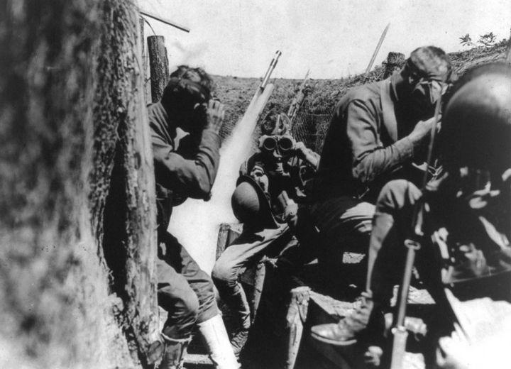 Американские солдаты надевают противогазы в окопе. За ними взлетает сигнальная ракета