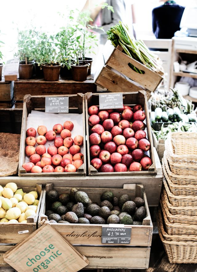Picturesque farmer's market with crates and baskets, apples and lemons.