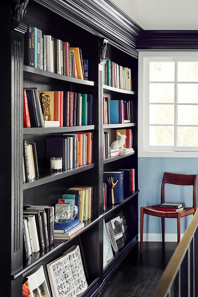 A black bookshelf is a great trick to make colorful books pop. In this home library, recommended reading in saturated shades orange and blue adds richness and depth to the room.