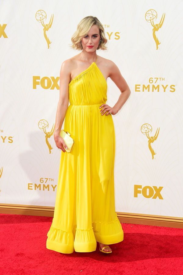 The magic in Taylor Schilling's bright Stella McCartney dress lies in the details. A pleated neckline is dotted by tiny golden beads, strung together (and held up) by a tiny strap that runs across the back. The skirt's tiered hem resembles that of a petticoat that balloons up with every twirl — and reveals Schilling's matching lemon Stuart Weitzman sandals. #refinery29 http://www.refinery29.com/2015/09/94113/celebrity-best-dressed-emmys-2015#slide-18