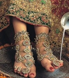 Serious ghungroos (foot jewels and bells) - Bride getting her feet washed with rose water infused milk.