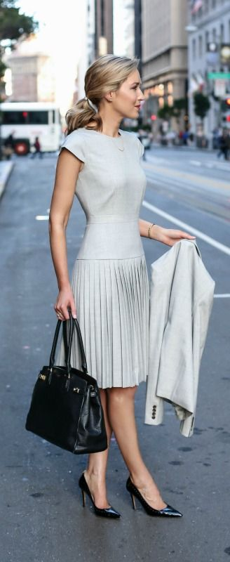 Grey knee length pleated dress, matching grey jacket, black pointed toe pumps, black work tote + barrette ponytail hairstyle